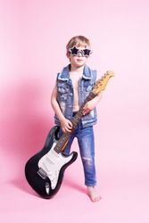 Pop culture: a boy with a guitar pretends to be a popular musician and perform a home concert.