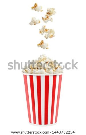 Popcorn falling into a red striped paper cup, isolated on white background
