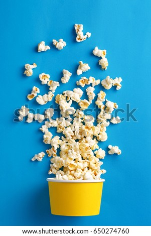 Popcorn. Flat lay of popcorn cup on a blue background. Top view