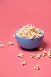 popcorn in a blue bowl on a pink background