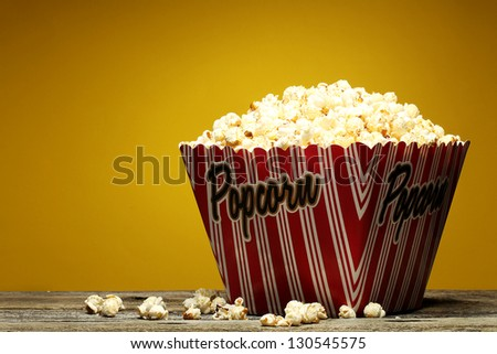 Popcorn in a container on a the yellow background.