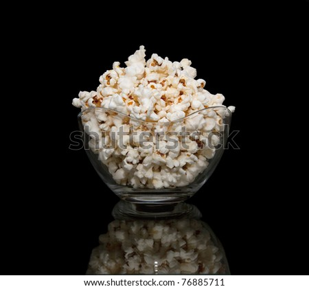 Popcorn in a glass pot , isolated on black background