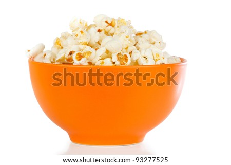 Popcorn in a orange bowl on a white background