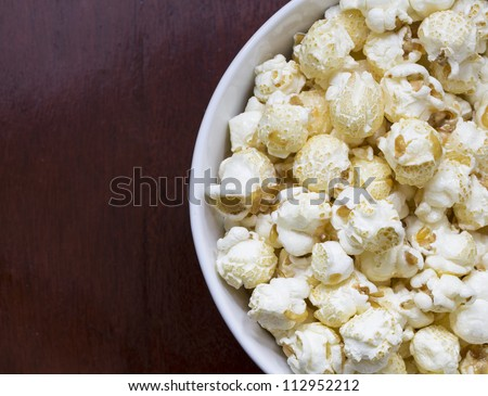 Popcorn in bowl on wood background
