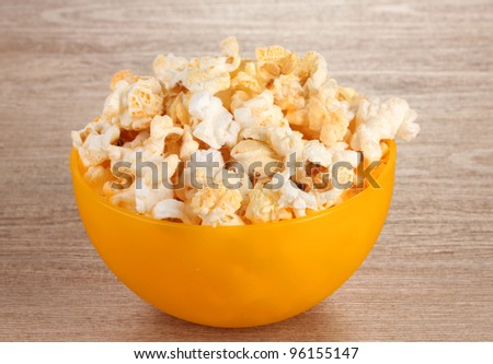 popcorn in bright plastic bowl on wooden table