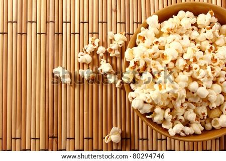 popcorn in brown bowl over mat