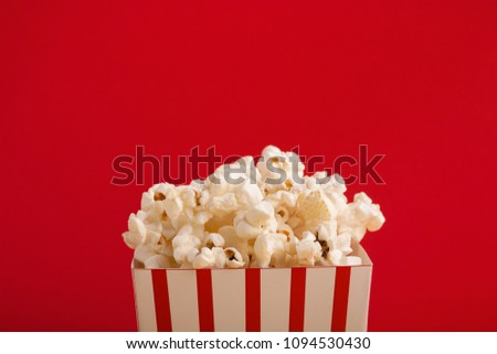 Popcorn in classic striped bukcet on red background. Fluffy maise paper box, copy space. Fast food and movie snack, entertainment concept #1094530430