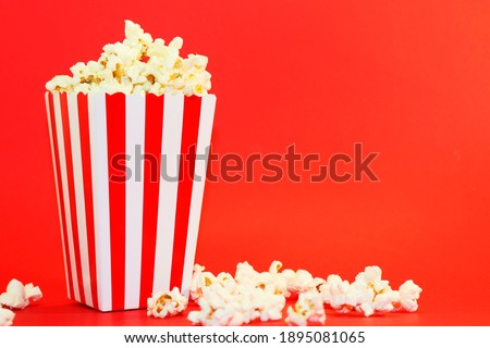 popcorn in paper packaging on a red background. Popcorn in red and white packaging. Cinema background