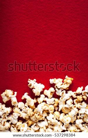 Popcorn popcorn on red textured background close up macro.