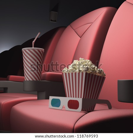 Popcorn, soda and 3D glasses on the seat, ready for the film.