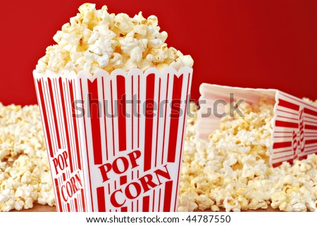 Popcorn still life of classic containers overflowing with freshly popped corn against a red background.  Macro with shallow dof.