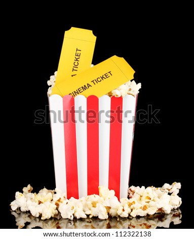 popcorn with cinema tickets isolated on black