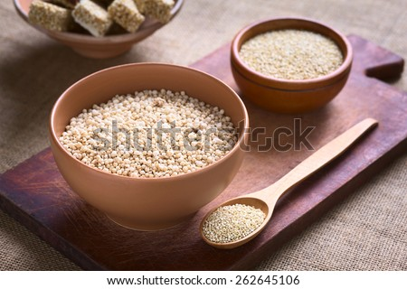 Popped white quinoa (lat. Chenopodium quinoa) cereal in bowl with raw quinoa seeds in the back photographed with natural light (Selective Focus, Focus one third into the quinoa cereal)
