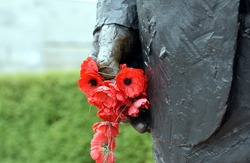 Poppies in a statue hand at the Australian War Memorial in Canberra.
