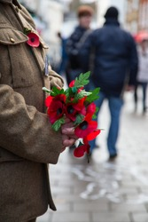 Poppy's in hands in shopping area for rememberence sunday.