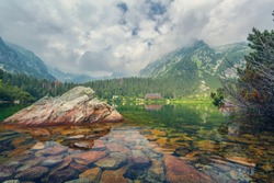 Popradske pleso in the High Tatras Mountains, Slovakia. Charming High Tatras with a forest on the slopes of the mountains and a hotel on the shore of the lake.