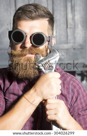 Poprtrait of young crazy man in purple checkered shirt and aviator glasses standing in garage holding iron metallized spanner near mouth on workshop background, vertical picture