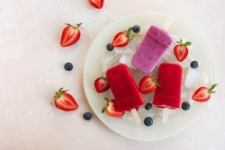 Popsicle with berries on plate with ice. Homemade ice cream with strawberry and blueberry on kitchen table. Refreshing summer dessert. Top view, flat lay, copy space