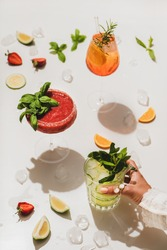 Popular bar summer ice alcoholic cocktails. Gin-tonic, Aperol Spritz and strawberry basil Margarita in glasses and womans hand holding glass over plain white background with cut fruits