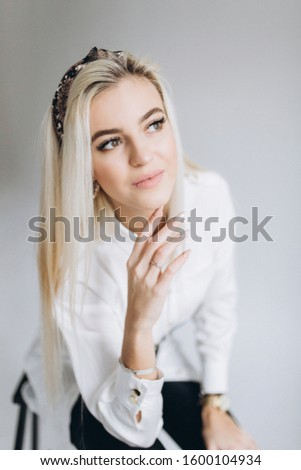 Popular beautiful blondie model actrees posing indoors in studio on white isolated background. Beauty, art, modeling concept