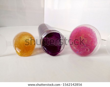 Popular children's toy Slime for hobbies and entertainment. Pink, yellow bright mucus with sparkles in round jars. #1562142856