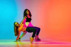 Popular dancing style. Two stylish modern girls dancing hip-hop on gradient blue orange background in neon. Active lifestyle idea. Concepth of modernity, youth, movement, style, dance, ad