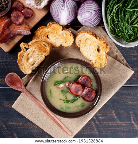 Popular dish of Portuguese cuisine called Caldo Verde. Made with potatoes, bacon, pepperoni sausage and kale. Top view Foto stock ©