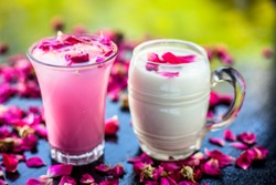 Popular Indian & Asian Summer drink on wooden surface i.e. Gulab falooda or gulab ka sherbat with some rose petals on black colored shiny surface.