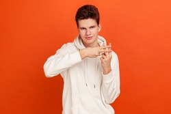 Popular male blogger in casual style sweatshirt with hood showing hashtag sign with fingers, recommending popular websites. Indoor studio shot isolated on orange background