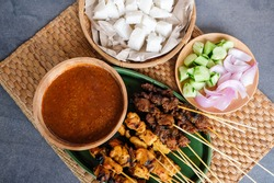 Popular Muslim street food. Chicken and Mutton Satay with Spicy Peanut Gravy Sauce. Eaten with raw onion, cucumber and ketupat also called steamed rice dumplings