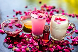 Popular Ramazan drink i.e. Rose falooda or rose shake in a transparent glass along with raw milk in another glass and honey,rose syrup and rose essence also present on the surface with rose petals.