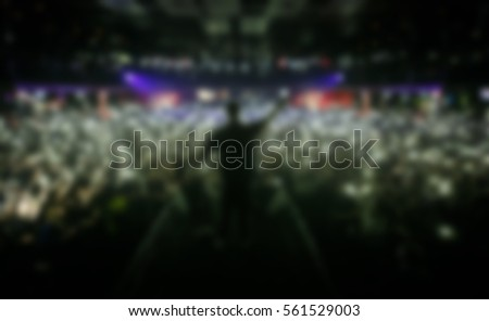 Popular rap singer sing on scene in nightclub.Big music show concert in the club.Bright stage lighting,crowded dancefloor.Rapper singing live.Entertainment event
