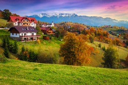 Popular rural touristic places with spectacular gardens and high snowy mountains in background. Autumn landscape with deciduous trees and houses on the hill, Magura, Transylvania, Romania, Europe