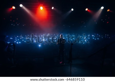 Popular singer in front of crowd on scene in night club. Bright stage lighting, crowded dance floor. Phone lights at concert. Band blue silhouette crowd. People with cell phone lights.