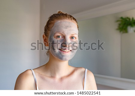 Popular spa treatment bubbling mask with charcoal oxygen purifying product on the face of beautiful girl with green eyes, beauty treatments at home