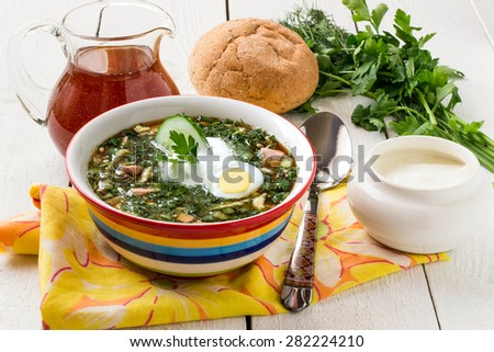 Popular spring cold soup okroshka with kvass. Okroshka in a bright bowl, sour cream, kvass in a jug, a spoon, bread and herbs on white wooden table. Selective focus
