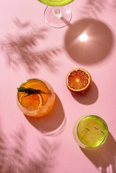 Popular summer ice alcoholic cocktails served under the summer sun light, view from above. Trendy retro style with shadows.