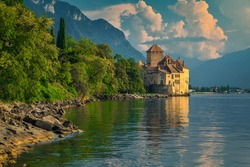 Popular Swiss touristic location with famous picturesque Chillon castle at Geneva lake and high mountains in background at sunset, Montreux, Switzerland, Europe