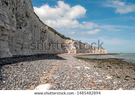 Popular tourist attraction and relax by the ocean concept with wide chalk wall made of white cliffs on warm summer day and waves hitting the rocks on shoreline in Broadstairs, Kent, United Kingdom