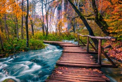 Popular touristic wooden bridge in the colorful autumn deep forest. Wooden promenade with clean brook and spectacular waterfalls, Plitvice National Park, Croatia, Europe