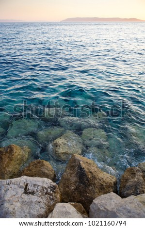 Popular travel destination for summer vacation travel.Beautiful sunset light on the beach.Crystal clear water washes rocky shore of Adriatic Sea in Croatia.Awesome sea scape view