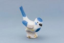 Porcelain bird figure on a blue background.