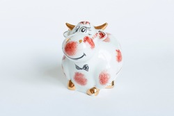Porcelain bull figurine in white and red color on a white background. New year of the bull