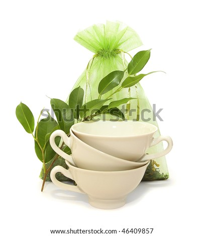 porcelain cups, green twigs and silk bag of tea on a white background