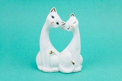 Porcelain figurine of two white cats. On a turquoise background