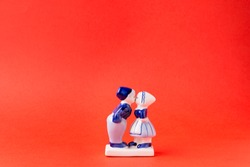 Porcelain figurines of kissing boy and girl in national Dutch costumes on red background. Saint Valentine's Day Concept.