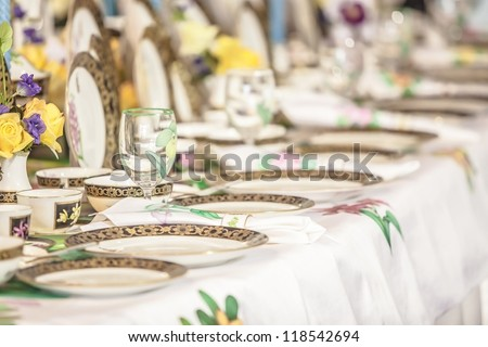 Porcelain set of plates, dishes, utensils, and water glasses. selective focus on transparent glass