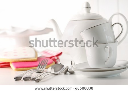 Porcelain teapot with cups and valentine cookies in background