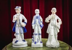 Porcelain, vintage, old-fashioned figurines on red background.