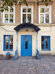 Porch and front door painted in bright blue color. Vintage doorway and framed windows of building exterior. Classical architecture details